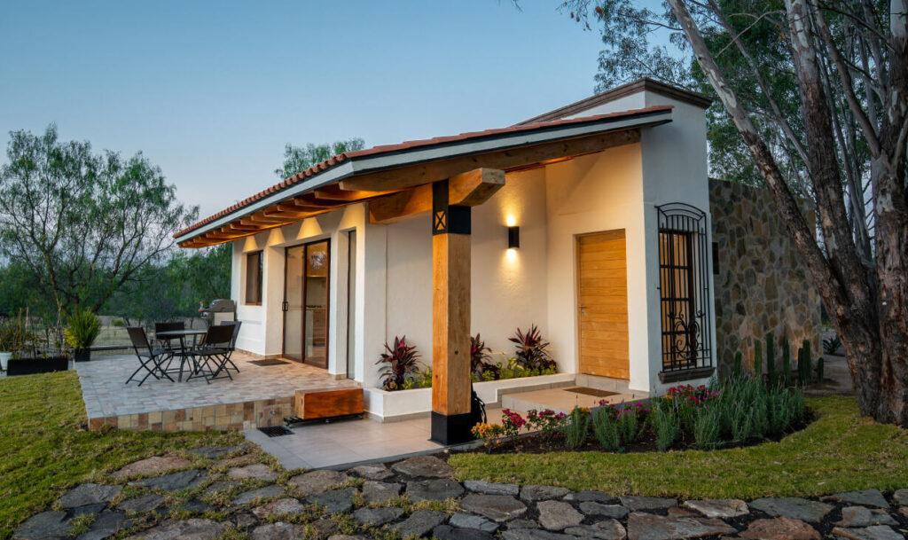 Terreno con jardín y fachada de Casa Jacinto, una casa con acabado campestre, diseñada y construida por A4 Arquitectura