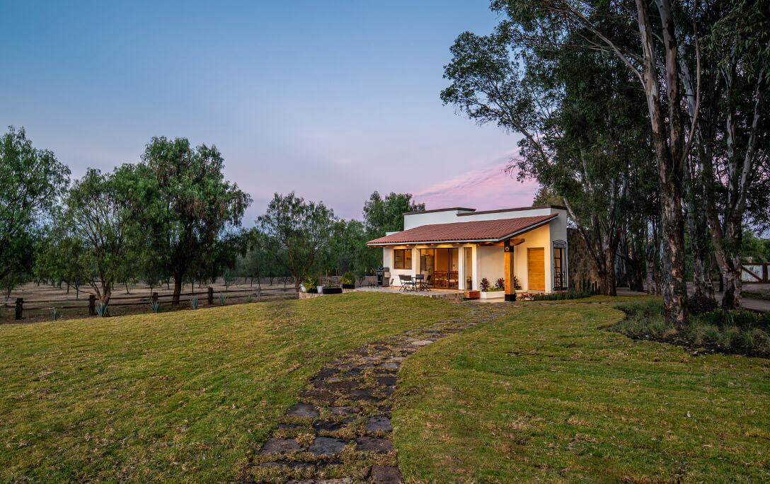 Terreno con jardín y árboles, y fachada de Casa Jacinto, una casa con acabado campestre, diseñada y construida por A4 Arquitectura