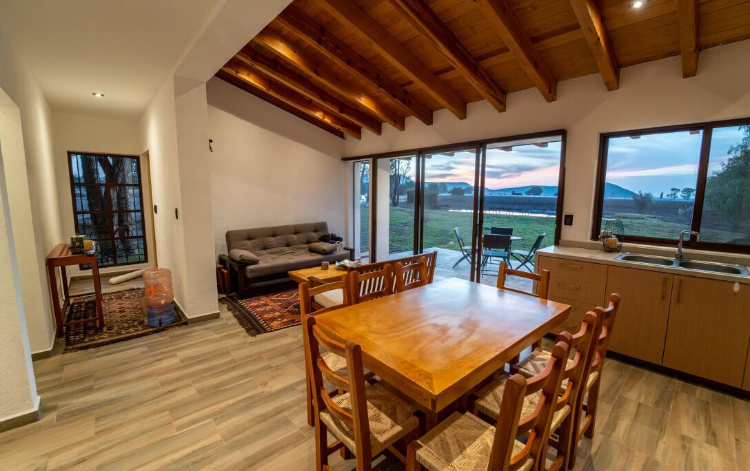 Sofá y comedor con sillas en Casa Jacinto, una casa con acabado campestre, diseñada y construida por A4 Arquitectura