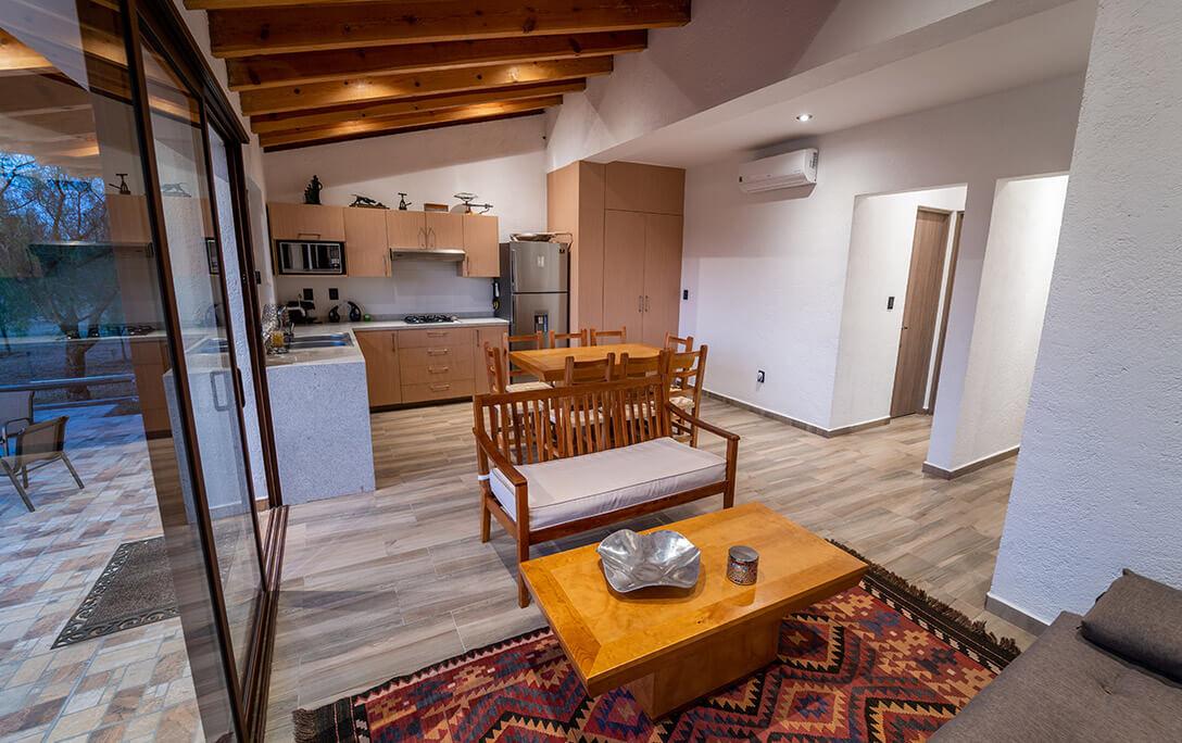Sofá, comedor con sillas y cocina con refrigerador en Casa Jacinto, una casa con acabado campestre, diseñada y construida por A4 Arquitectura