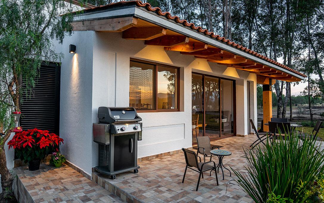 Plantas, silla, mesa y cobertizo en terraza de Casa Jacinto, una casa con acabado campestre, diseñada y construida por A4 Arquitectura