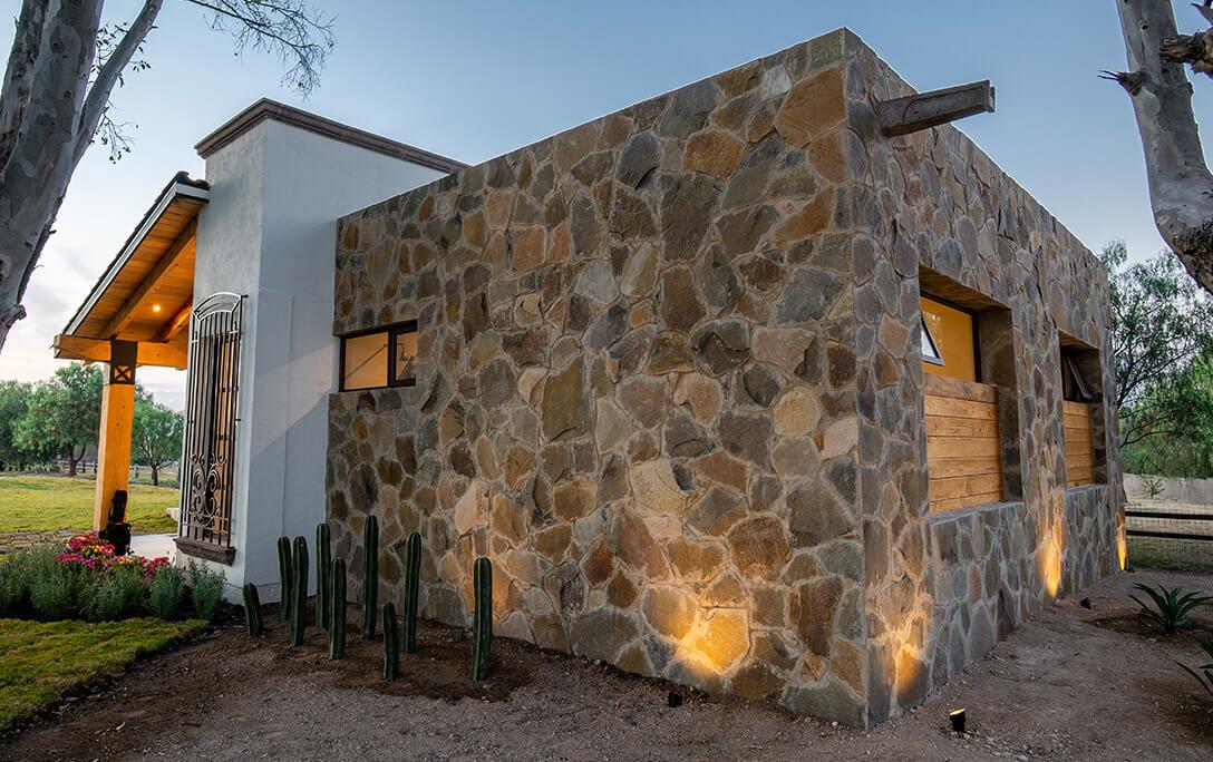 Muro de piedra roca en fachada de Casa Jacinto, una casa con acabado campestre, diseñada y construida por A4 Arquitectura