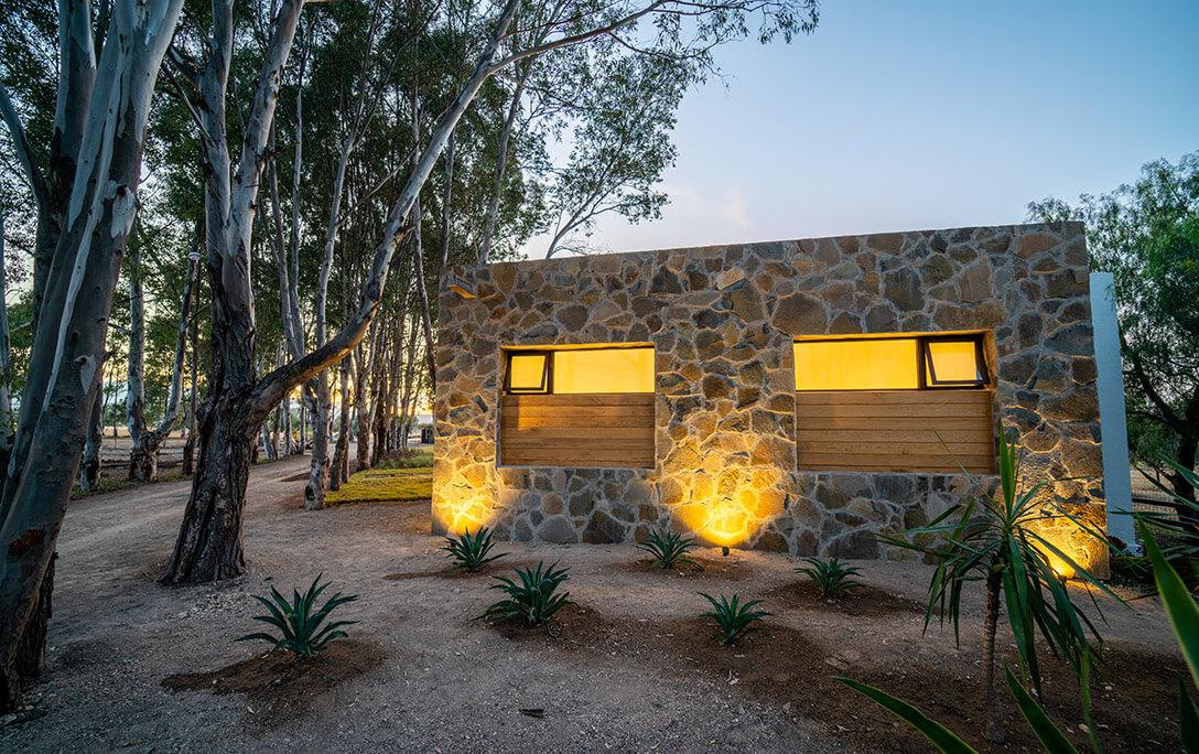 Plantas, árboles y muro de piedra roca en fachada de Casa Jacinto, una casa con acabado campestre, diseñada y construida por A4 Arquitectura
