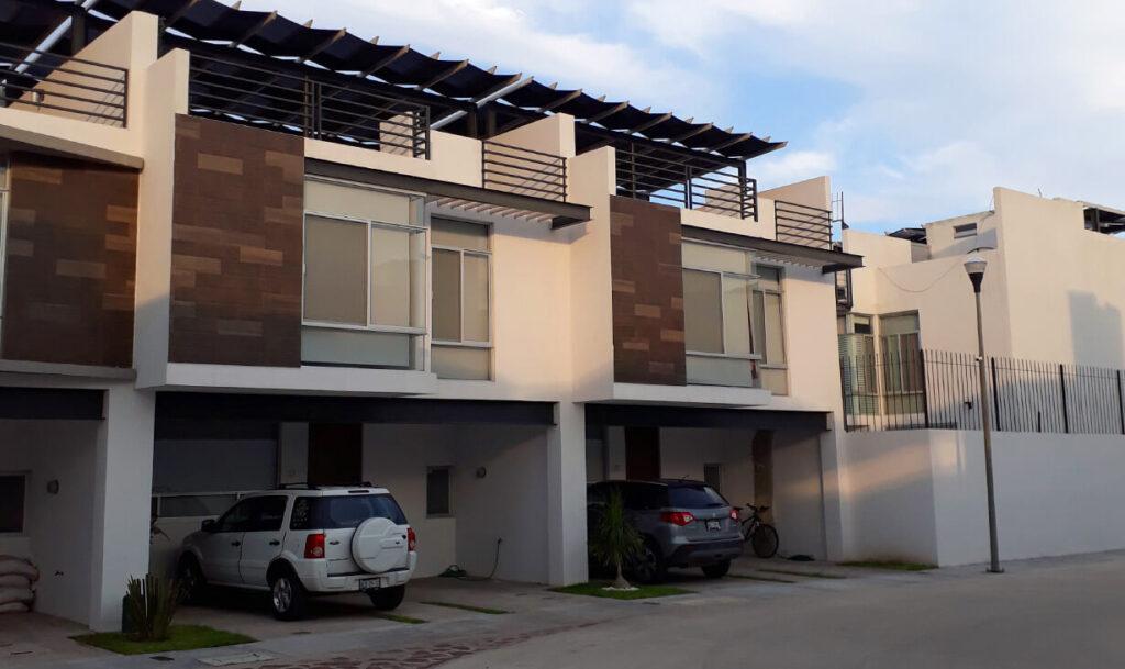 Fachadas de casas blancas y autos en el condominio residencial Empoli Terranova, un conjunto de casas construidas por A4 Arquitectura