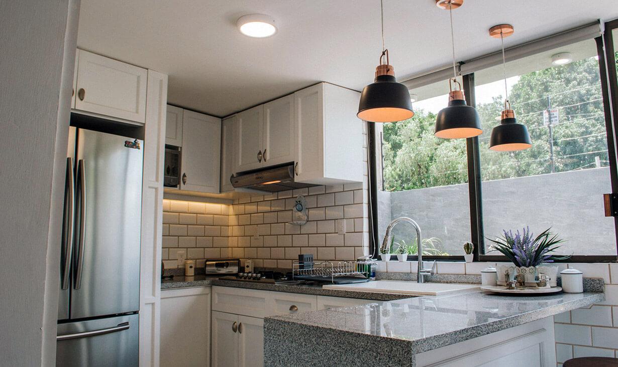 Encimera, refrigerador y lámparas de Cocina Calesa, donde se realizó remodelación y diseño de interiores, por A4 Arquitectura